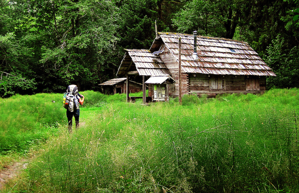 A hiker approaches the Olympus Ranger Station along the Hoh River trail in Olympic National Park. The trail starts in the mossy and lush Hoh Rain Forest then climbs over 5,000 ft. in elevation along towering trees and rock to overlook the windswept Blue Glacier on Mt. Olympus. Tracing your steps back to the Hoh River visitors center the hike covers over 36 miles of diverse climate and ecosystems ranging from temperate rain forest to alpine.