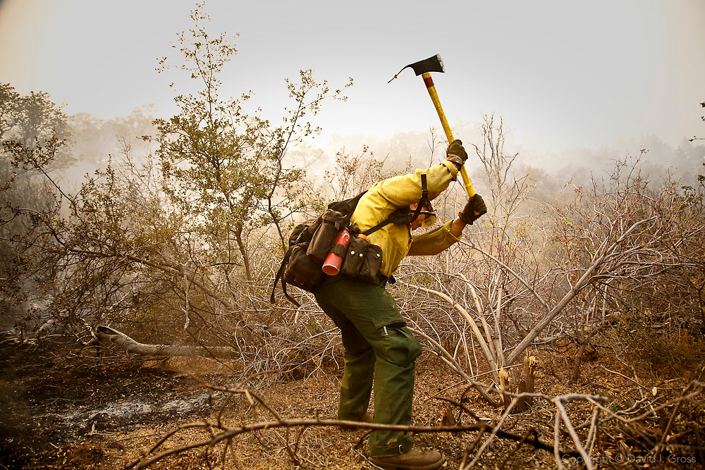 A Forest Service Hotshot ??? firefighter clears a three foot (90cm) line down to bare soil around an errant fire that has jumped the fire break. Much of the dangerous work is performed by elite ground crews in steep terrain with 55 lb. (25 kg) packs, 25 lb.(11 kg) chainsaws, shovels and rakes, and two gallons (3.78 l) of water for a ten hour shift.