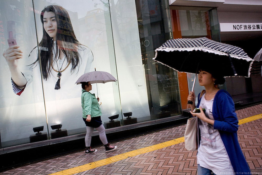 Women pass in front of a mobile phone advertisment in a rainy day at Shibuya area of Tokyo.