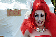 A Drag-Queen with bright red hair at The Rainbow Pride Event in Yoyogi Park, Shibuya, Tokyo, Japan. Sunday, April 26th 2015. This is the forth annual celebration of LGBT issues in Tokyo and forms part of a wider Rainbow Week. About 5% of the Japanese population identify as homosexual and this event hopes to foster a society where they can live equally and without prejudice.