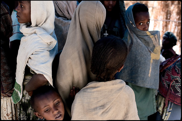 """Childs and boys at the celebration of an early marriage. In Ethiopia survives the practice of forced child marriage, despite is forbidden by the law. A wedding can cost up to 15,000 birr (1,500 USD) in the countryside - a lot of money in a country where nearly 50 percent of the population lives on less than a dollar a day. North West of Ethiopia, on friday, Febrary 13 2009.....In a tangled mingling of tradition and culture, in the normal place of living, in a laid-back attitude. The background of Ethiopia's """"child brides"""", a country which has the distinction of having highest percentage in the practice of early marriages despite having a law that establishes 18 years as minimum age to get married. Celebrations that last days, their minds clouded by girls cups of tella and the unknown for the future. White bridal veil frame their faces expressive of small defenseless creatures, who at the age ranging from three to twelve years shall be given to young brides men adults already...To protect the identities of the recorded subjects names and specific places are fictional."""