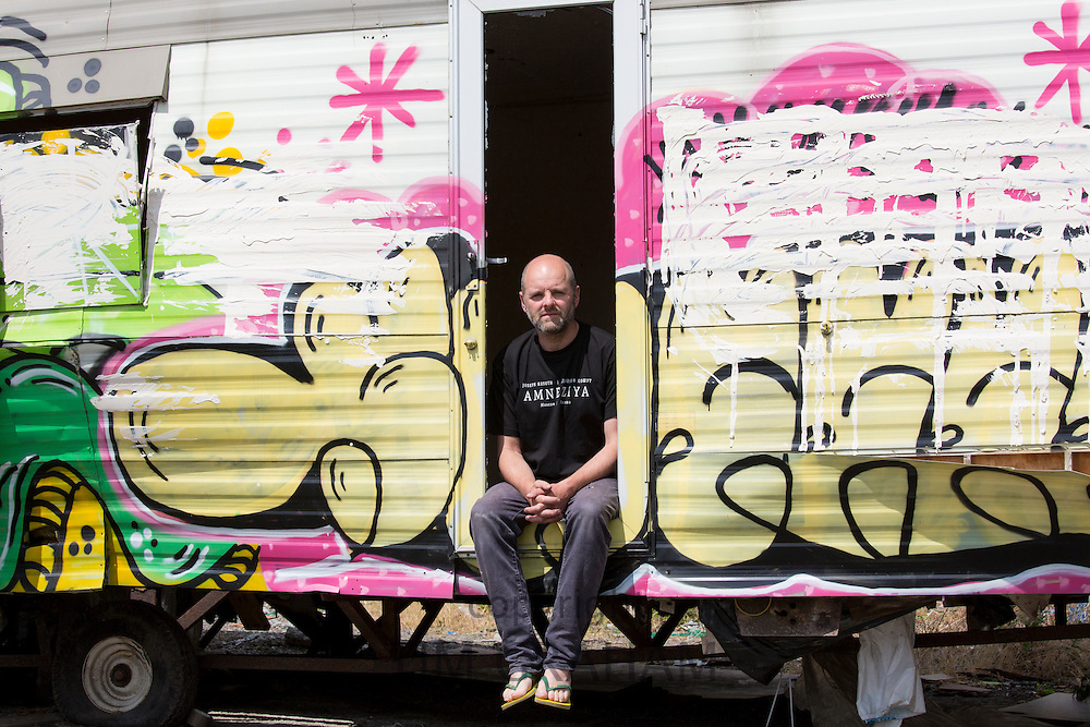 Gavin Turk, artist, photographed with a caravan on wasteland near his East London studio -------COPYRIGHT - TIM GRAHAM. For permission to use  this image please contact mail@timgraham.co.uk