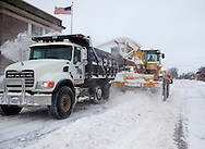 Grinnell city workers haul away snow plowed to the middle of the street in Grinnell, Iowa on Wednesday February 2, 2011.