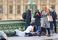 Passers by treat a victim on Westminster Bridge following the Terror Attack
