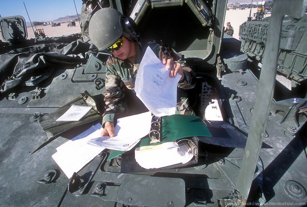 PFC Jay Thompson, a driver of the Army's new Stryker medium weight armored vehicle, sort through manuals at the National Training Center in Ft. Irwin, Calif. on Friday, July 26, 2002. The army has only had the Stryker for a month and this is their debut in maneuvers at 'war' at Ft. Irwin for the Millennium Challenge 2002 Experiment (MCO2)...The Stryker has a communictions package, called the FBCB2 that enables them to transmit and receive data on their position, the position of other FBCB2 equiped vehicles, still shots from unmanned aerial vehicles, and data from higher command. This will help improve their intelligence knowledge and share in real time with other units...As part of the military transformation MC02 is testing all branches of the military in the largest ever live and virtual battle being played out across the nation through August 15, 2002. The goal is to see how well the different branches operate together under a joint command that shares intelligence and resources in an effort to put the right forces in the right place at the right so as to minimze the amount of fighting that is necessary to protect U.S. interests abroad.
