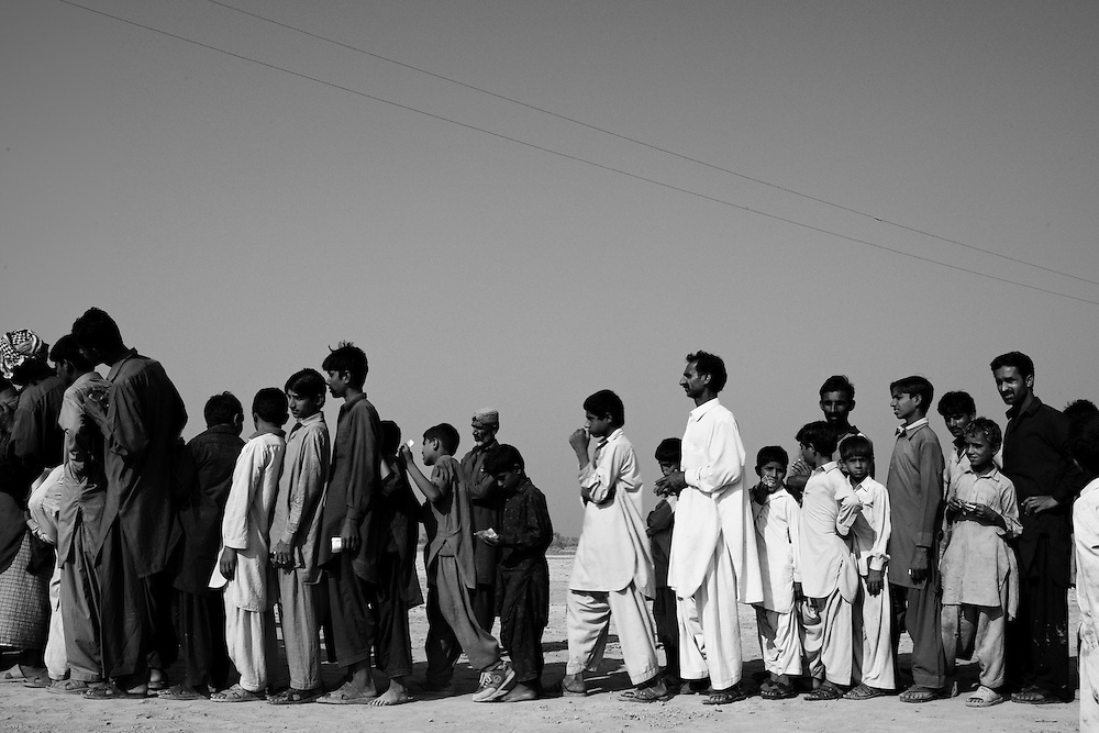 Men and children line up for registration as hygiene kits are distributed by Medicins Sans Frontieres in the village of Qadir Bur Jatsi, Union Council Dasti, Jacobabad, Sindh Province on November 11, 2012. The village was affected by flooding between 2010 and 2012. People's homes were destroyed as waters rose with house collapsing on inhabitants. The livelihoods of the villagers were also affected as many traditionally work in the surrounding fields as agricultural laborers. With this land now damaged or under water they are forced to work as daily wage laborers in the city of Jacobabad close by. This work is generally intermittent and many of the villagers find it difficult to earn to support their families. The stagnant water also attracts mosquitoes where they breed and increases the spread of malaria within the local population. MSF distributed 140 hygiene kits within the village. More than five million people were affected by flooding caused by September's monsoon rains in Pakistan, the majority of those in Sindh Province. MSF responded within the district of Jacobabad with programs focusing on water and sanitation, mobile health clinics, distribution of non food items and hygiene kits.