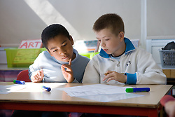 Two boys sitting at desk in classroom working on maths problem,