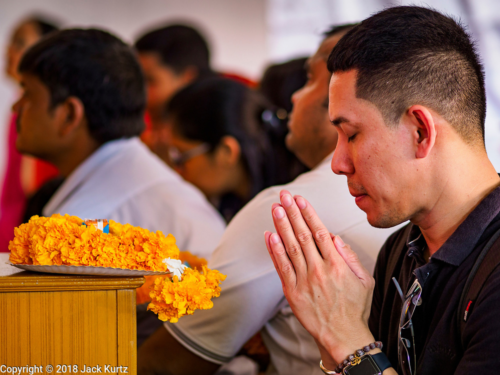 """23 SEPTEMBER 2018 - BANGKOK, THAILAND:  A man prays at the Ganesha Festival at Wat Dan in Bangkok. Ganesha Chaturthi also known as Vinayaka Chaturthi, is the Hindu festival celebrated on the day of the re-birth of Lord Ganesha, the son of Shiva and Parvati. The festival, also known as Ganeshotsav (""""festival of Ganesha"""") is observed in the Hindu calendar month of Bhaadrapada, starting on the the fourth day of the waxing moon. The festival lasts for 10 days, ending on the fourteenth day of the waxing moon. Outside India, it is celebrated widely in Nepal and by Hindus in the United States, Canada, Mauritius, Singapore, Thailand, Cambodia, and Burma.    PHOTO BY JACK KURTZ"""