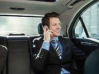 Mid adult businessman sitting at back seat of car using mobile phone