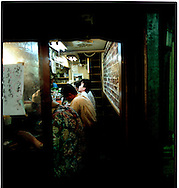 """Men in small """"izakaya"""" restaurant that serves fresh seafood, Shinjuku, Tokyo, Japan."""
