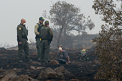 "November 15, 2018 - Paradise, California, U.S.: Arrested for trying going home! Paradise resident, CHARLIE MILES, 27, was sitting cross legged on the ground in handcuffs, with state rangers around him, after being arrested for trying to go home, Thursday. Miles, was on a desolate stretch of Skyway Road about halfway between his family's home, in the devastated town of Paradise and the church shelter in Chico, where he has been sleeping on a cot. His crime was trying to go back home. Miles was trying to see if anything was left of his and his parents trailers. Miles rose on the morning of Nov. 8 at 5:45 am. ""I had coffee with my parents like I always do,"" he said. ""Then I was brushing my teeth and I looked up at the sky and it was gray. At that point, I started packing their stuff."" The flames soon chased them. ""I was forced to drag everyone off the property,"" he said. ""My dad was helping my mom and I was carrying their belongings. There were trees exploding. People were trying to drive their cars out but they couldn't. We have lost absolutely everything we owned,"" The officers drove him back to the Chico City limits and set him free. ""They didn't give me a ticket or anything,"" Miles said. He said a friend was able to return to their street and told him, everything is gone. Miles and his parents are but one of scores of victims of the deadliest wildfire in California history, the Camp Fire started Nov. 8th at crack of dawn, its death toll grew today to 77, while the number of people unaccounted is over thousand people. The blaze is now, two-thirds contained, after consuming some 150,000 acres. (Credit Image: © Renee C. Byer/Sacramento Bee via ZUMA Wire)"