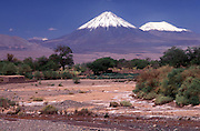 Snow-capped volcanoes mark the border between Chile and Bolivia, seen from the Atacama desert oasis town of San Pedro de Atacama. Chile