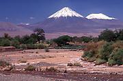 Snow-capped volcanoes mark the border between Chile and Bolivia, seen from the Atacama desert oasis town of San Pedro de Atacama. Chile