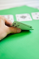 Cropped shot of hand holding aces of hearts and clubs on green surface