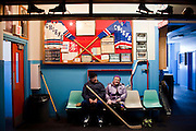 HOUGHTON, MI -DEC. 12, 2014: Bob Makolin, 85, and his wife Bertha Makolin, 85, sit beneath memorabilia for a portrait in the Calumet Colosseum in Calumet, MI Friday, Dec. 12, 2014. The Calumet Colosseum is the oldest hockey rink in existence and the two visit three days a week for exercise and to socialize. Lauren Justice for The New York Times