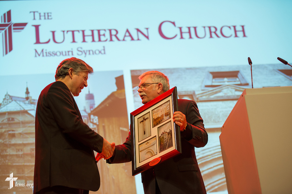 The Rev. Dr. Michael Kumm, chairman of the LCMS Board of Directors, presents a framed group of photographs of the Old Latin School to artist Hartmut Rademann during a reception at the Stadthaus following the dedication of The International Lutheran Center at the Old Latin School on Sunday, May 3, 2015, in Wittenberg, Germany. LCMS Communications/Erik M. Lunsford