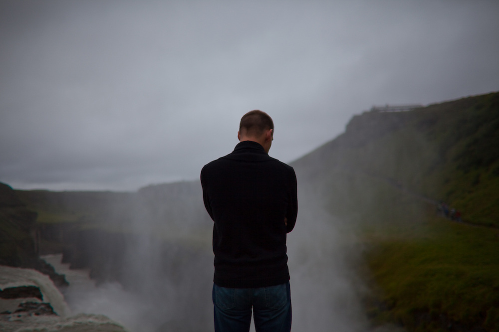 "A man observes the Hvita River as it crashes down Gulfoss, a massive waterfall located along the ""Golden Circle,"" Iceland."