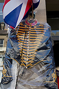 An army cavalry uniform from history hanging in a plastic covering outside an Army Surplus business, on 28th June 2019, in Coldstream, Scotland.