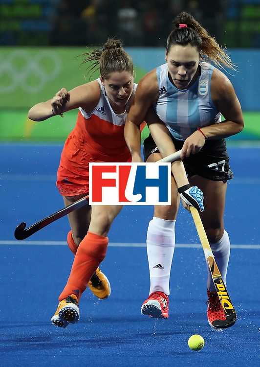 RIO DE JANEIRO, BRAZIL - AUGUST 15:  Marloes Keetels #8 of Netherlands and Noel Barrionuevo #27 of Argentina chase the ball during the quarter final hockey game on Day 10 of the Rio 2016 Olympic Games at the Olympic Hockey Centre on August 15, 2016 in Rio de Janeiro, Brazil.  (Photo by Christian Petersen/Getty Images)