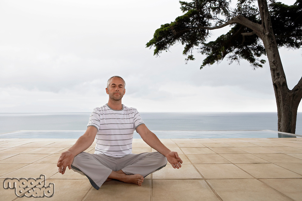 Man sitting in yoga position on terrace by infinity pool