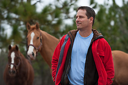 Man in a red jacket standing with two horses in the background