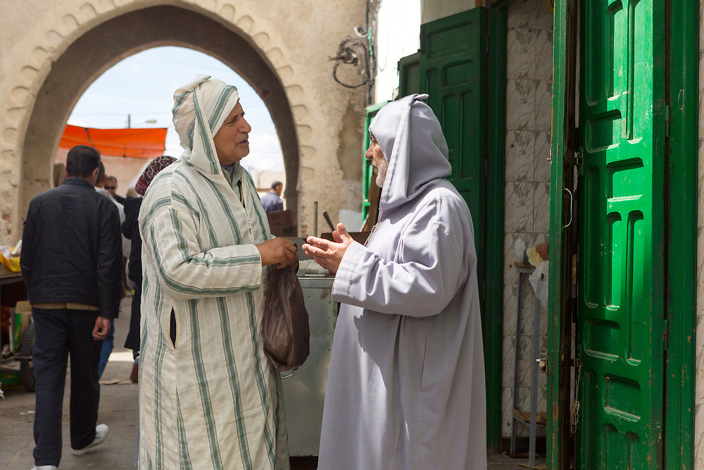 TETOUAN, MOROCCO - 5th April 2016 - Two local elderly men wearing traditional Moroccan djellabas chat in a street in the Tetouan Medina, Rif region of Northern Morocco.