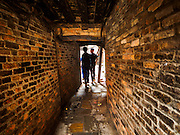 01 AUGUST 2015 - KATHMANDU, NEPAL: A brick tunnel leads into a residential courtyard in Kathmandu. After earthquake, the tunnel was propped up with timbers. The Nepal Earthquake on April 25, 2015, (also known as the Gorkha earthquake) killed more than 9,000 people and injured more than 23,000. It had a magnitude of 7.8. The epicenter was east of the district of Lamjung, and its hypocenter was at a depth of approximately 15 km (9.3 mi). It was the worst natural disaster to strike Nepal since the 1934 Nepal–Bihar earthquake. The earthquake triggered an avalanche on Mount Everest, killing at least 19. The earthquake also set off an avalanche in the Langtang valley, where 250 people were reported missing. Hundreds of thousands of people were made homeless with entire villages flattened across many districts of the country. Centuries-old buildings were destroyed at UNESCO World Heritage sites in the Kathmandu Valley, including some at the Kathmandu Durbar Square, the Patan Durbar Squar, the Bhaktapur Durbar Square, the Changu Narayan Temple and the Swayambhunath Stupa. Geophysicists and other experts had warned for decades that Nepal was vulnerable to a deadly earthquake, particularly because of its geology, urbanization, and architecture.          PHOTO BY JACK KURTZ