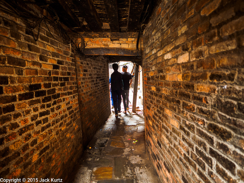 01 AUGUST 2015 - KATHMANDU, NEPAL: A brick tunnel leads into a residential courtyard in Kathmandu. After earthquake, the tunnel was propped up with timbers. The Nepal Earthquake on April 25, 2015, (also known as the Gorkha earthquake) killed more than 9,000 people and injured more than 23,000. It had a magnitude of 7.8. The epicenter was east of the district of Lamjung, and its hypocenter was at a depth of approximately 15km (9.3mi). It was the worst natural disaster to strike Nepal since the 1934 Nepal–Bihar earthquake. The earthquake triggered an avalanche on Mount Everest, killing at least 19. The earthquake also set off an avalanche in the Langtang valley, where 250 people were reported missing. Hundreds of thousands of people were made homeless with entire villages flattened across many districts of the country. Centuries-old buildings were destroyed at UNESCO World Heritage sites in the Kathmandu Valley, including some at the Kathmandu Durbar Square, the Patan Durbar Squar, the Bhaktapur Durbar Square, the Changu Narayan Temple and the Swayambhunath Stupa. Geophysicists and other experts had warned for decades that Nepal was vulnerable to a deadly earthquake, particularly because of its geology, urbanization, and architecture.          PHOTO BY JACK KURTZ