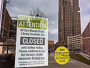 "16 MARCH 2020 - DES MOINES, IOWA: A sign on the door to the Des Moines Public Library announcing the library's closure Monday. Sunday night, the Governor announced that the state health department had recorded ""community spread"" in Des Moines. The Iowa Department of Public Health has urged all public buildings, like libraries and schools, to close, and restaurants to switch to take out or delivery only. The State Capitol instituted mitigation measures that included mandatory health screening for everyone going into the building, canceling group tours of the building, and closing the souvenir shop and snack bar.      PHOTO BY JACK KURTZ"