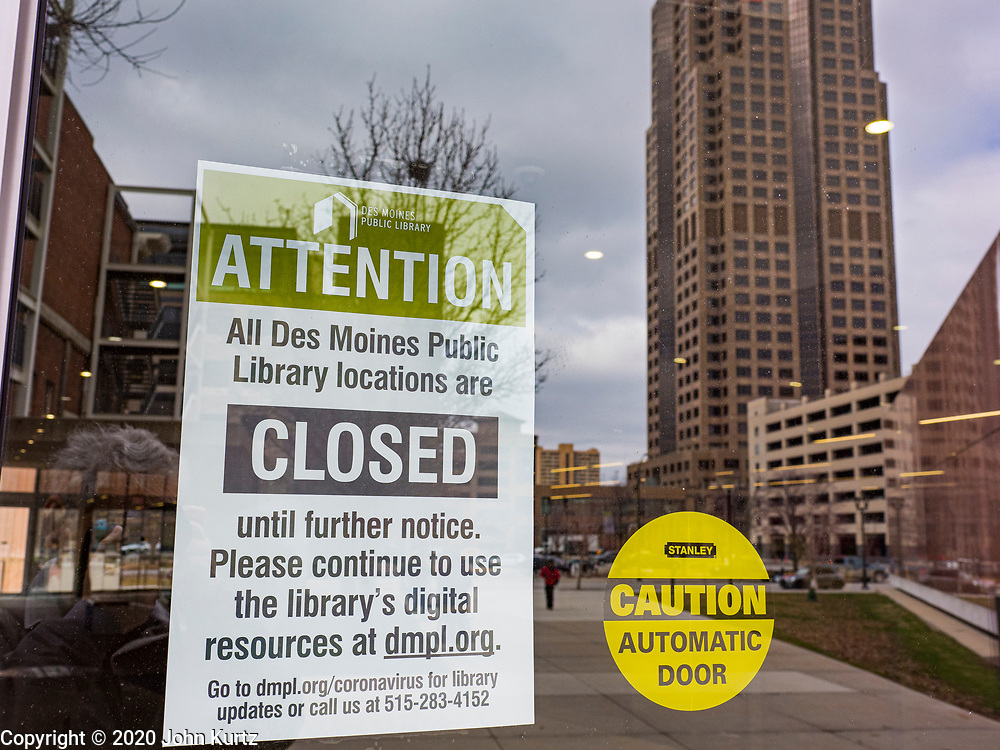 """16 MARCH 2020 - DES MOINES, IOWA: A sign on the door to the Des Moines Public Library announcing the library's closure Monday. Sunday night, the Governor announced that the state health department had recorded """"community spread"""" in Des Moines. The Iowa Department of Public Health has urged all public buildings, like libraries and schools, to close, and restaurants to switch to take out or delivery only. The State Capitol instituted mitigation measures that included mandatory health screening for everyone going into the building, canceling group tours of the building, and closing the souvenir shop and snack bar.      PHOTO BY JACK KURTZ"""