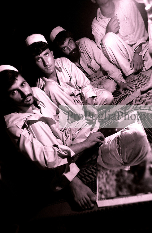 Afghan students look at a picture of a woman displayed in a photographic book on Kashmir