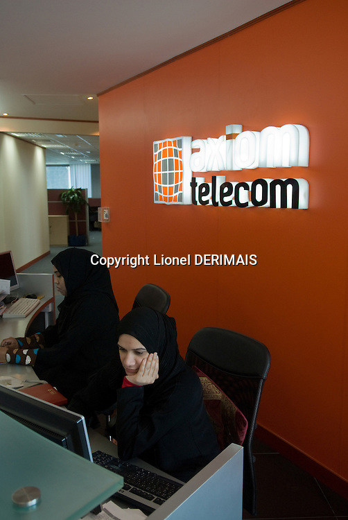 Woman wearing the traditional abaya at the reception of Axiom Telecom offices. Dubai, one of the seven emirates and the most populous of the United Arab Emirates sits on the southern coast of the Persian gulf.