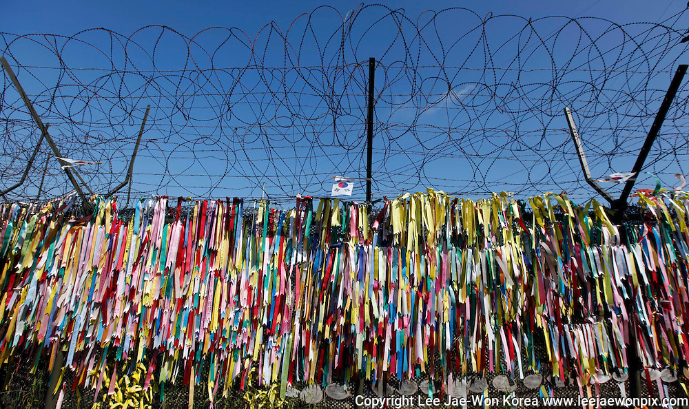 Ribbons bearing messages wishing for unification of the two Koreas hang on a barbed-wire fence at the Imjingak pavilion, near the demilitarized zone (DMZ) which separates the two Koreas in Paju, north of Seoul September 30, 2012, on the occasion of Chuseok, the Korean Thanksgiving Day. Chuseok is a time for Korean families to remember and honour their dead ancestors and Imjingak pavilion is the closest residents of the capitalist south can get to the border with the communist north. /Lee Jae-Won