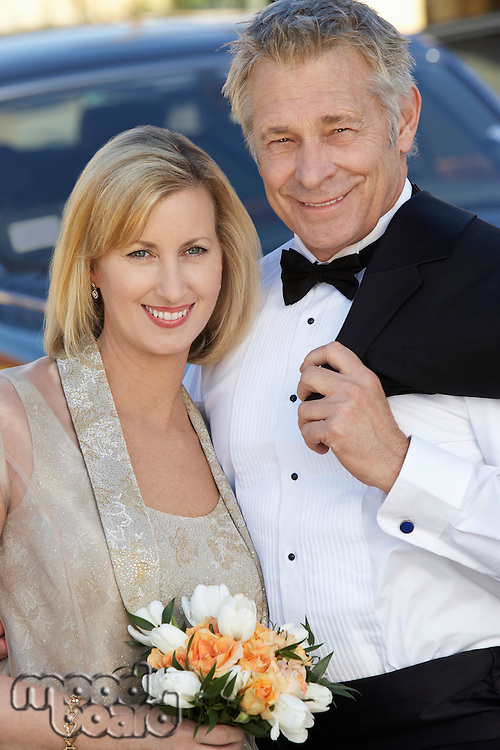 Middle-aged couple in formal wear in front of limousine, portrait