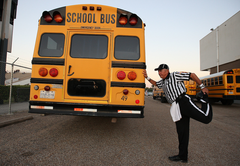 Umpire Dave Orton stretches by a school bus before officiating a high school football game between Pasadena Memorial and Deer Park, Thursday, October 20, 2011 at Veterans Memorial Stadium in Pasadena, TX.