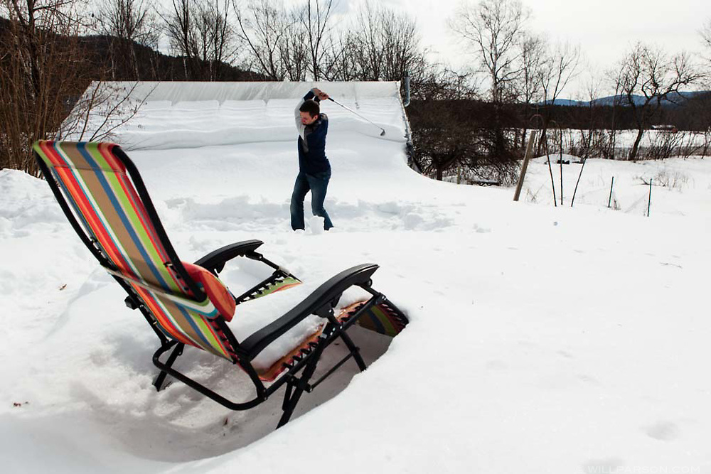 """Rivendell High School senior Josh Marshall hits a handful of golf balls from a small mat of artificial grass in the snow at his home in Orford, N.H., on March 26, 2014. """"I guess I'm getting pretty anxious,"""" said Marshall, who bought the mat in December and has used it 10-15 times this winter. (Valley News - Will Parson)"""