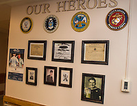 Belknap County Nursing Home's Veteran's wall with photos of John Neylon U.S. Marines,  Dana Aloise U.S. Army and Sheldon MacKnight U.S. Navy taken during their years of service in the United States Military.  (Karen Bobotas/for the Laconia Daily Sun)