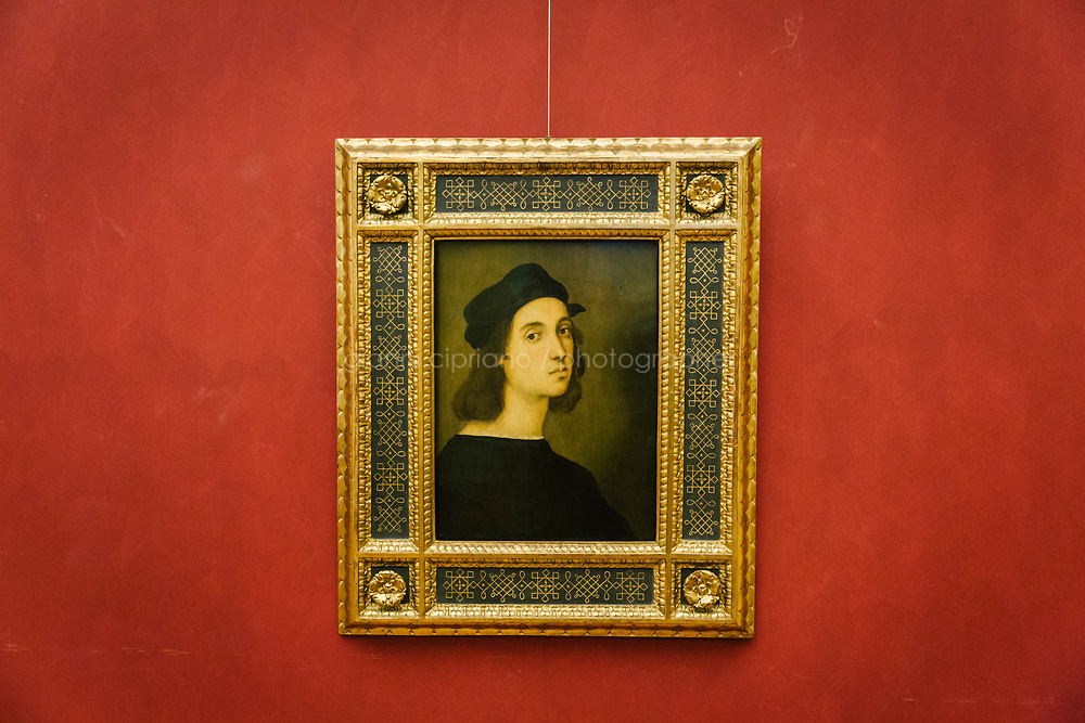FLORENCE, ITALY - 3 JUNE 2018: &quot;Self-Portrait&quot; (1504-1506 ca) by Raphael is seen here at the Uffizi before being relocated at Palazzo Pitti, in Florence, Italy, on June 3rd 2018.<br /> <br /> As of Monday June 4th 2018, Room 41 or the &ldquo;Raphael and Michelangelo room&rdquo; of the Uffizi is part of the rearrangement of the museum's collection that has<br /> been defining Uffizi Director Eike Schmidt&rsquo;s grander vision for the Florentine museum.<br /> Next month, the museum&rsquo;s Leonardo three paintings will be installed in a<br /> nearby room. Together, these artists capture &ldquo;a magic moment in the<br /> first decade of the 16th century when Florence was the cultural and<br /> artistic center of the world,&rdquo; Mr. Schmidt said. Room 41 hosts, among other paintings, the dual portraits of Agnolo Doni and his wife Maddalena Strozzi painted by Raphael round 1504-1505, and the &ldquo;Holy Family&rdquo;, that Michelangelo painted for the Doni couple a year later, known as the<br /> Doni Tondo.