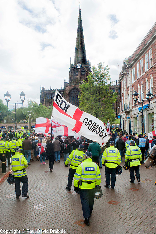 EDL members and supporters escorted by Police officers approach Rotherham Minster during Saturdays EDL rally in South Yorkshire  in Rotherham Town Centre <br />
