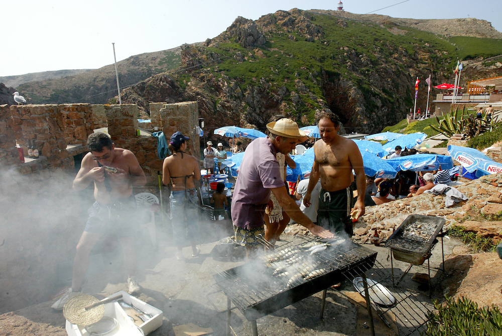 """People eating sardines from a common griller at Berlenga island, a marine reserve and classified by the Council of Europe as a """"Biosphere Reserve"""",  is now becoming an environmentally sustainable island from power generation, water, wastewater and solid waste treatment/recycle to reducing pollution at the source. This portuguese atlantic archipelago consists of a large island,  Berlenga Grande, rose granite made, and some small islands and rocks (Estelas and Farilhões), which are situated some 15 km off the headland of Cabo Carvoeiro to the north-west of Peniche, which is about 100 km north of Lisbon  .PHOTO PAULO CUNHA/4SEE"""
