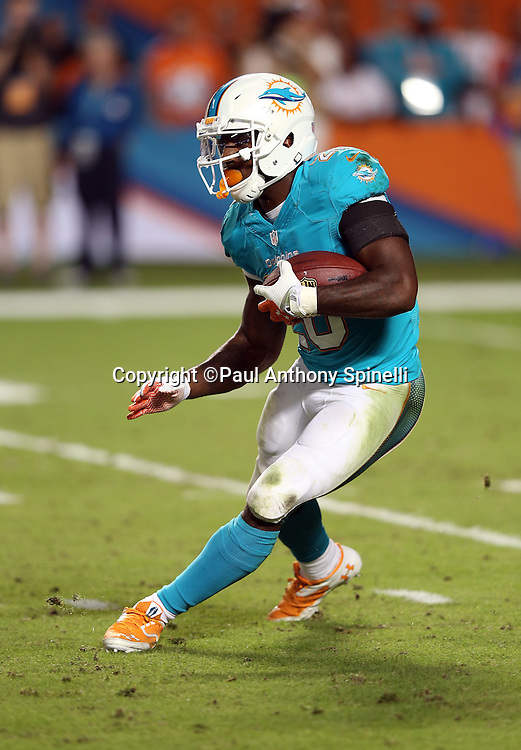 Miami Dolphins running back Lamar Miller (26) runs the ball during the NFL week 9 football game against the Cincinnati Bengals on Thursday, Oct. 31, 2013 in Miami Gardens, Fla.. The Dolphins won the game 22-20 in overtime. ©Paul Anthony Spinelli