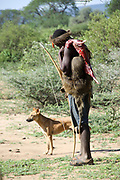 Datoga men hunting with bow and arrow with dog. Photographed at Lake Eyasi, Tanzania