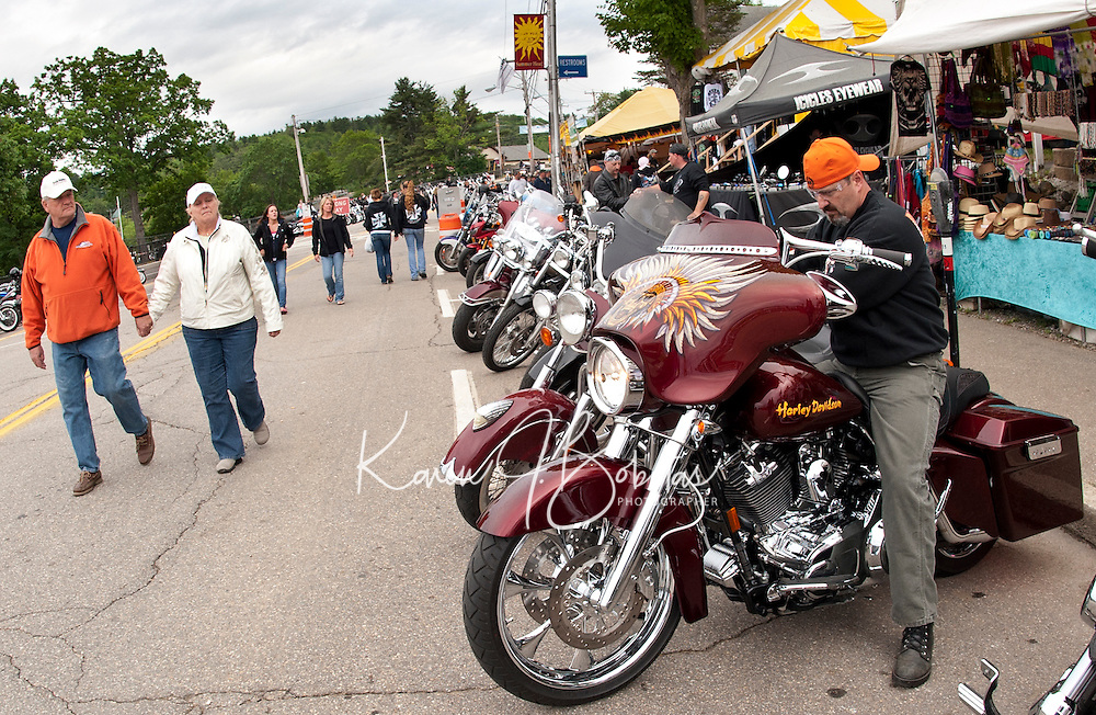 Les and Diane Cartier take a stroll down Lakeside Avenue Tuesday evening to look at the bikes lining the street.  The cold, damp weather has made for a quiet week so far at the 2011 Laconia Motorcycle Rally.  (Karen Bobotas/for the Laconia Daily Sun)