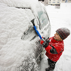 A young boy cleans snow off of the family car during a snowstorm in Portsmouth, New Hampshire.