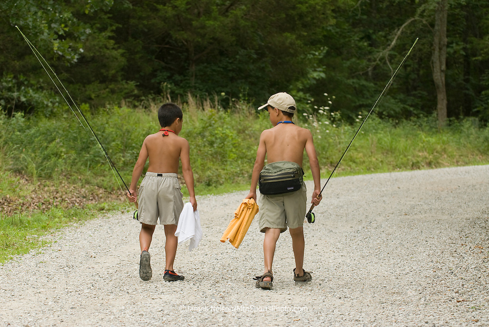 Nine- and seven-year-old brothers walk home after a day of fly fishing on the James River, Missouri.