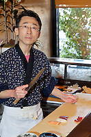 Portrait of a mature chef preparing sushi