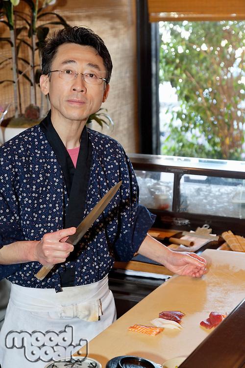 Portrait of a mature chef preparing sushi
