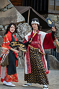 "Costumed Japanese samurai & woman with parasol and fan. Matsumoto Castle is a ""hirajiro"" - a castle built on plains rather than on a hill or mountain, in Matsumoto, Nagano Prefecture, Japan. Matsumotojo's main castle keep and its smaller, second donjon were built from 1592 to 1614, well-fortified as peace was not yet fully achieved at the time. In 1635, when military threats had ceased, a third, barely defended turret and another for moon viewing were added to the castle. Interesting features of the castle include steep wooden stairs, openings to drop stones onto invaders, openings for archers, as well as an observation deck at the top, sixth floor of the main keep with views over the Matsumoto city."