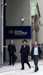 Pedestrians and diamond dealers make their way past a synagogue which is next to the Antwerp Diamond Bank, on Hoveniersstraat in the heart of the diamond district in Antwerp, Belgium, on Wednesday August 26, 2009. (Photo © Jock Fistick)