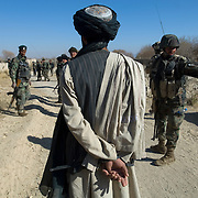 Dec 16, 2007 - Zhari District, Kandahar, Afghanistan - A  man believed to be a Taliban insurgent who was captured and detained by British Gurkha and Afghan soldiers is lead up a road during Operation Terrah Toorah in the Siah Choy area in Zhari District located west of Kandahar City, Afghanistan. The operation was a Canadian lead effort in coordination with the Afghan National Army (ANA) and Royal Gurkha Rifles from the British Army. The Zhari district has become well known for insurgent activity and attacks on coalition forces..(Credit Image: © Louie Palu/ZUMA Press)